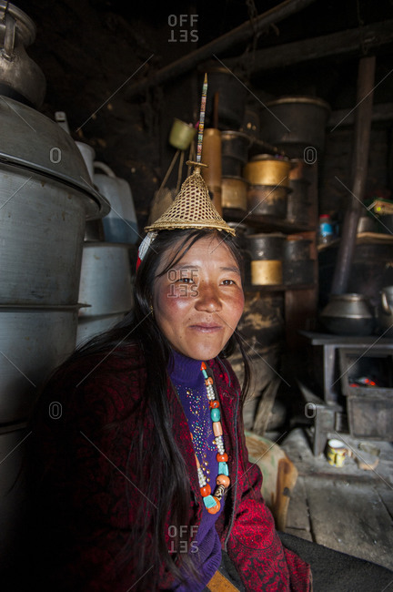 A Layap woman from the village of Laya wearing a tradition hat which features a unique spike made from bamboo sitting in her kitchen