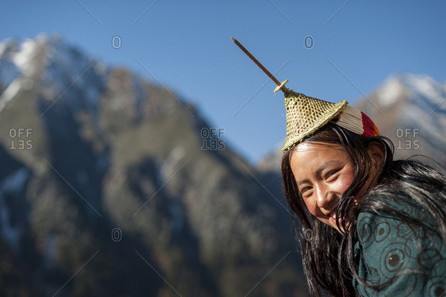 A Layap girl wearing a traditional conical shaped hat with a protruding bambook spike smiles for the camera in the remote village of Laya in Bhutan
