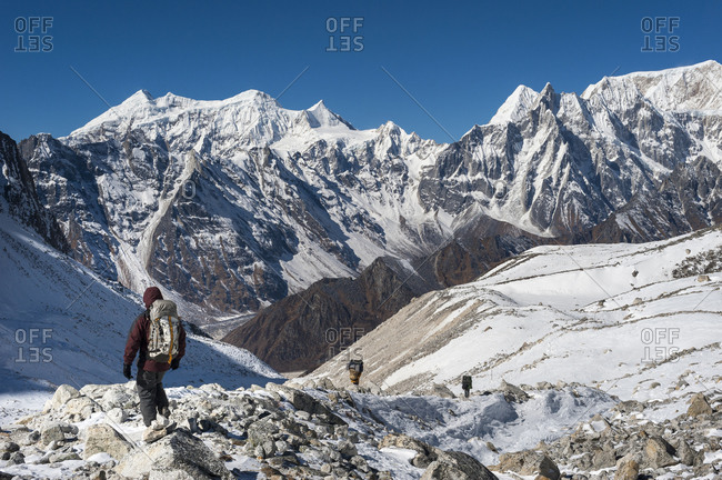 Porters and trekkers make their way across the Larke La with views looking west towards the Annapurnas