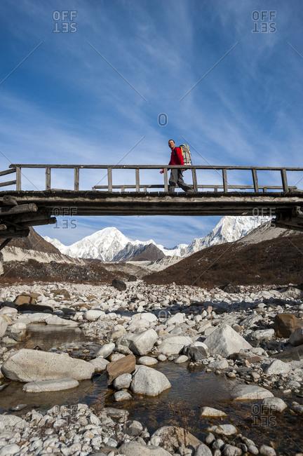 A trekker crosses the Dudh Khola on an old wooden log bridge