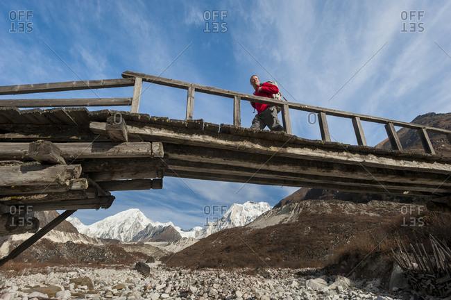 A trekker crosses the Dudh Khola on an old wooden log bridge in the Manaslu region of Nepal
