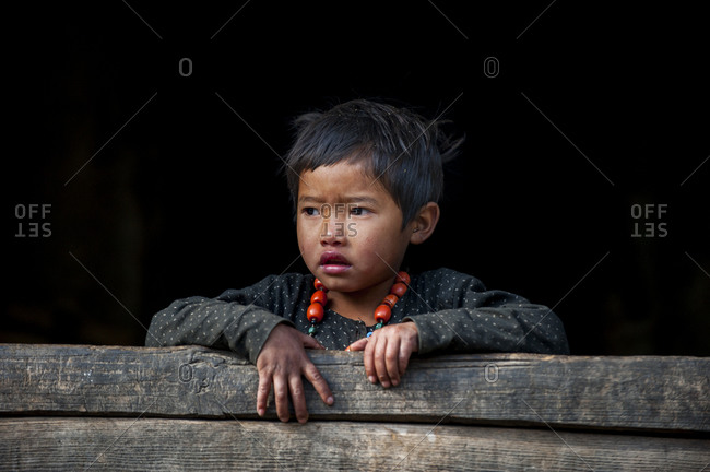 A little girl plays with her necklace in the Manaslu region