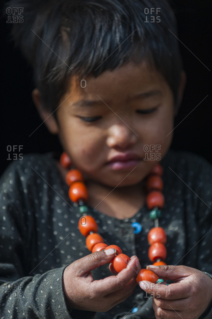 A little girl plays with her necklace in the Manaslu region of Nepal