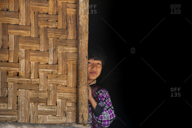 A little girl peeks around one of the bamboo walls of her house