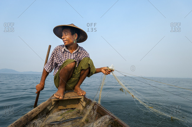 A fisherman casts his net on Indawgyi lake