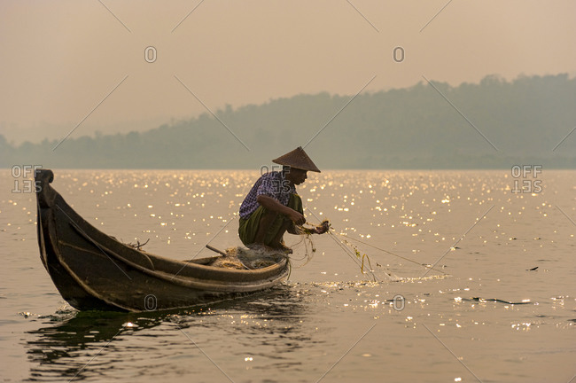 A fisherman pulls in his net on Indawgyi lake in Kachin State in Burma, also known as Myanmar