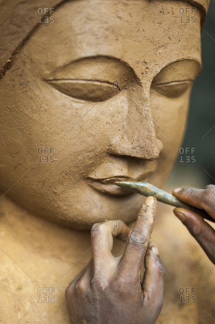A man sculps a Buddha from clay which will then be bronzed