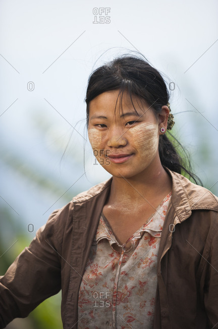 A young Burmese woman with Thanaka cream on her face. It's ground from tree bark and has been used by Burmese women to decorate their faces for thousands of years. It also acts as sun protection.