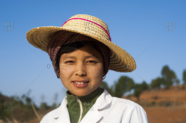 A Burmese woman takes a short break from harvesting wheat. The Thanaka cream on her face is from tree bark and has been used by Burmese women to decorate their faces for thousands of years. It also acts as sun protection.