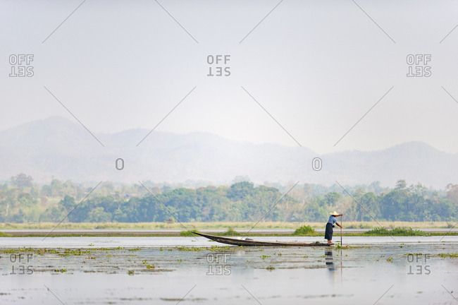 A fisherman on Inle lake paddles slowly through the shallow water