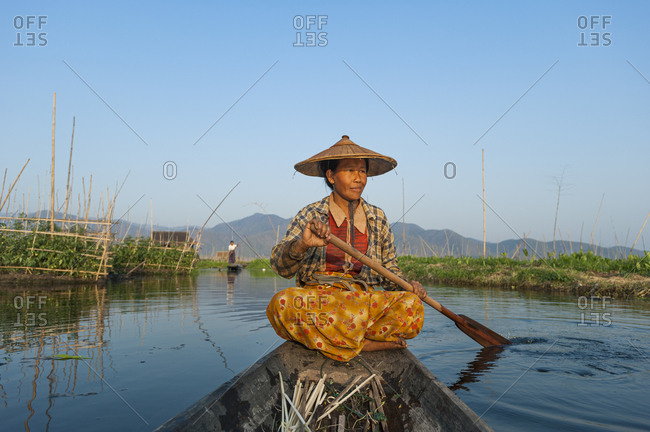 A woman paddles home through the floating gardens on Inle lake