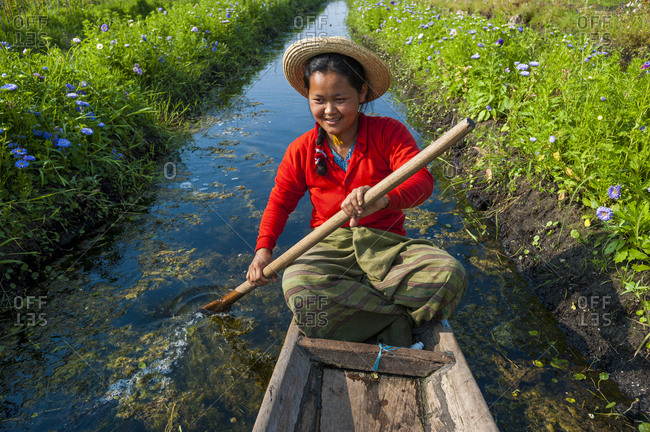 A woman paddles through the floating gardens on Inle lake