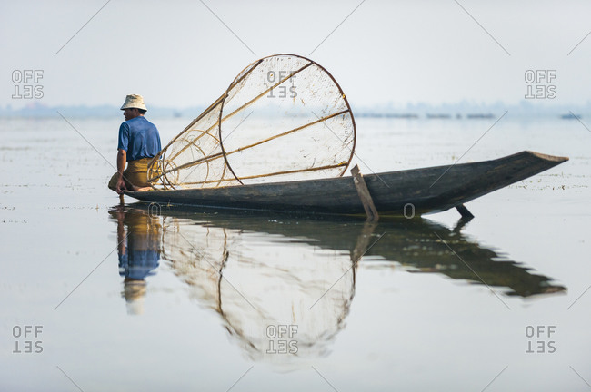 A basket fisherman scans the lake looking for fish in shallow water