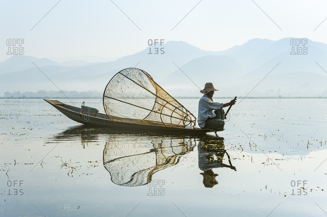 A basket fisherman on Inle lake scans the still and shallow water for signs of life and prepares to plunge his cone shaped net