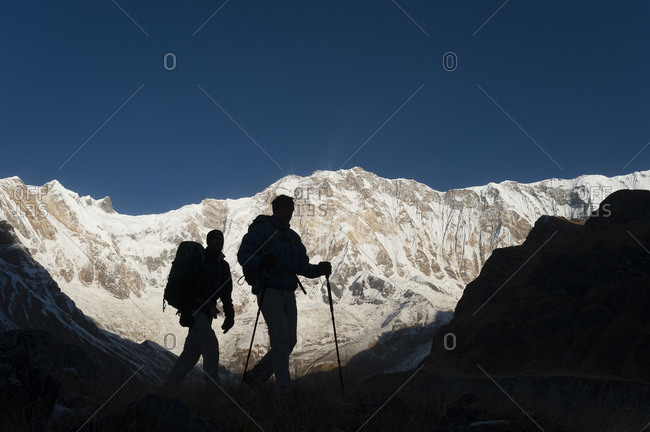 Trekkers on their way down from Annapurna base camp with views of Annapurna 1 in the distance