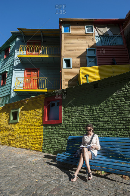 A tourist relaxes among the brightly painted houses of La Boca