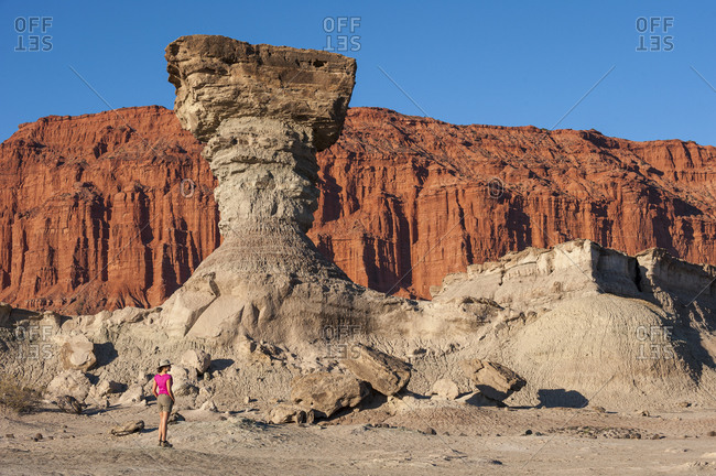 A woman stands beside eroded rock formations in the Ischigualasto park
