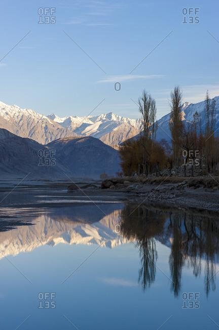 Karakoram range mountains reflected in the Shyok river