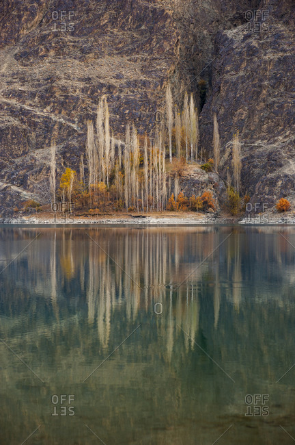 Reflected trees in the turquoise waters of Khalti lake