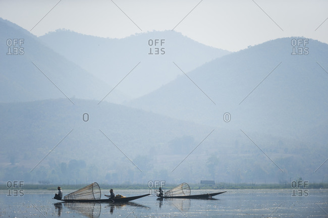 Basket fishermen scan Inle lake looking for fish in the shallow water