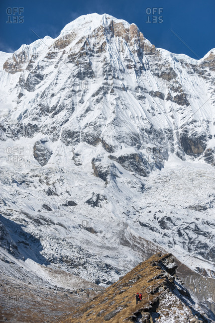 Two trekkers stand on the edge of the morraine and look into the Annapurna glacier