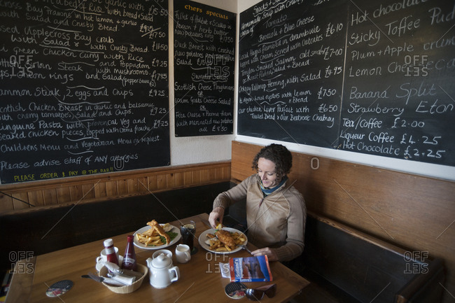 Applecross Bay, Western Highlands, Scotland - May 3, 2011: A woman eats traditional fish and chips in a cafe in Scotland