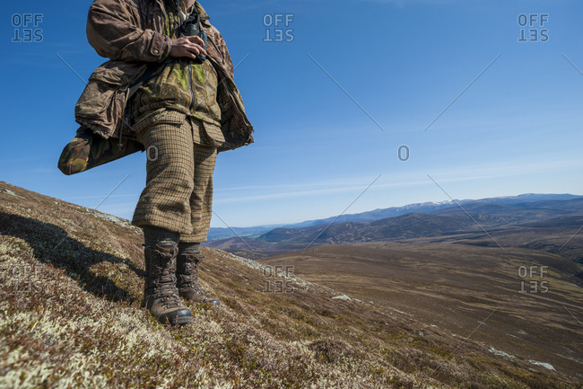 A man wearing traditionally Scottish dress looks out over a glen