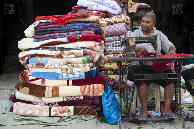 Surkhet, Mid Western region, Nepal - October 5, 2011: A man makes and repairs textiles on the street in Nepal