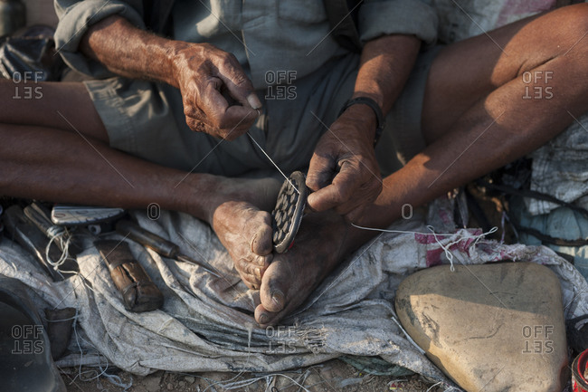 A man repairs shoes on the street in Nepal