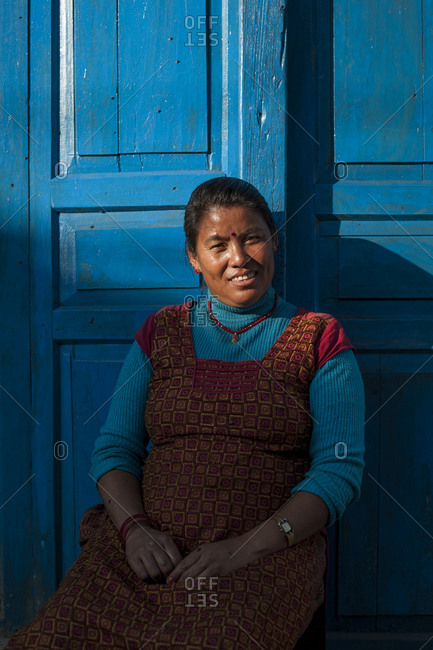 A woman sits outside her house and smiles for the camera