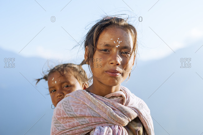 A little girl carries a baby in a rural village in western Nepal