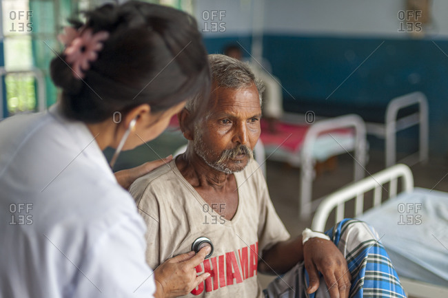 A doctor checks a mans chest with a stethoscope in a small hospital in Nepal
