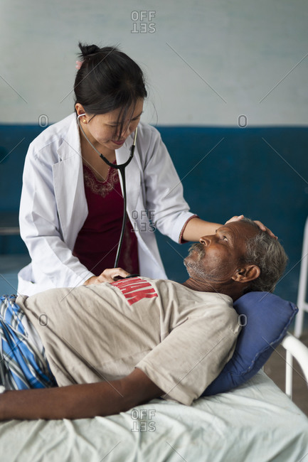 Kapilvastu District, Lumbini Province - October 18, 2011: A doctor checks a mans chest with a stethoscope in a small hospital in Nepal