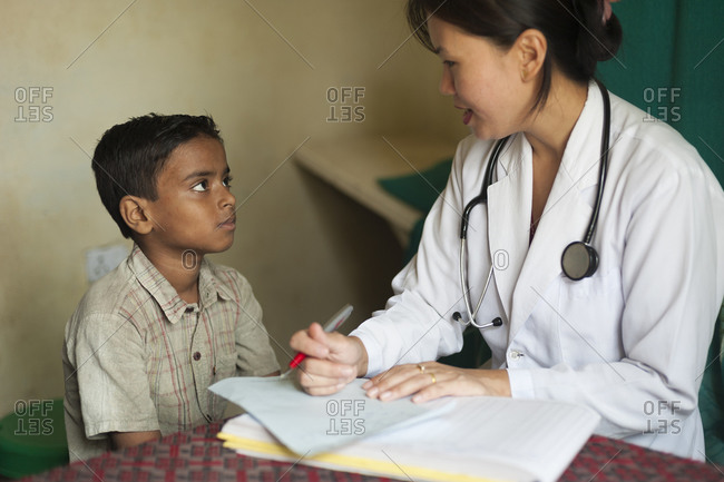 A doctor looks into a boys mouth in a rural hospital in Nepal