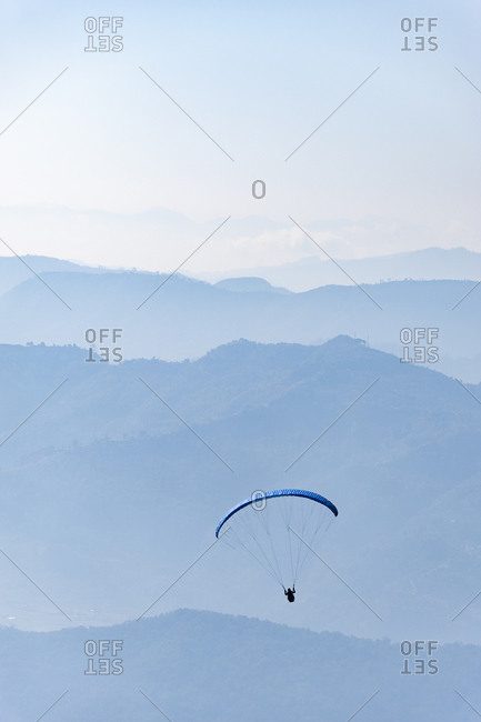 A paraglider flying above Pokhara with views of the Nepalese hills
