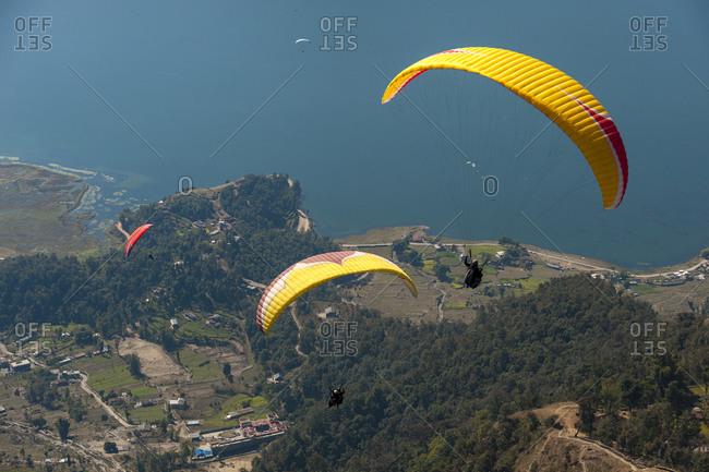 Paragliders flying above Phewa lake near Pokhara in Nepal