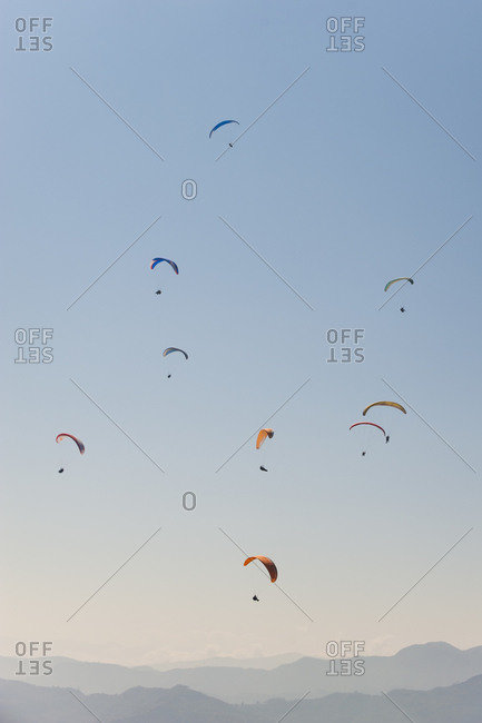 Paragliders get lift on the thermals above Pokhara in Nepal
