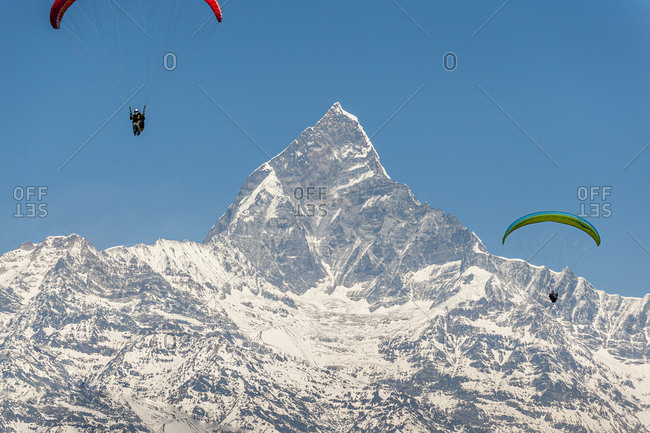 Paragliders hang in the air with the dramatic peak of Machapuchare also called Fishtail mountain in the distance