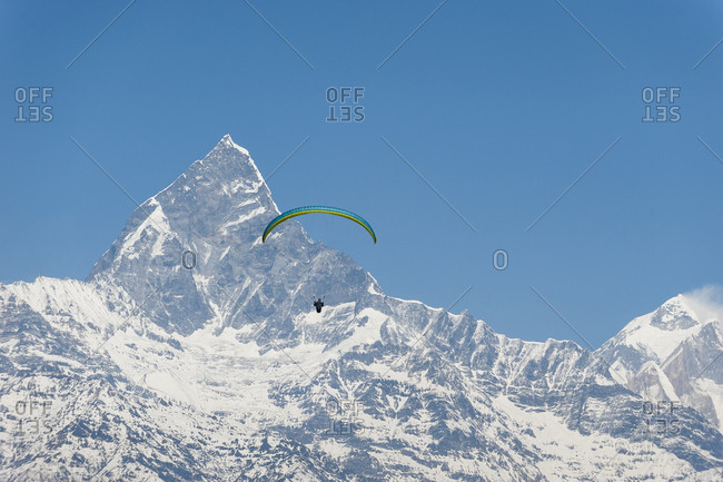 A paraglider hangs in the air with the dramatic peak of Machapuchare also called Fishtail mountain in the distance