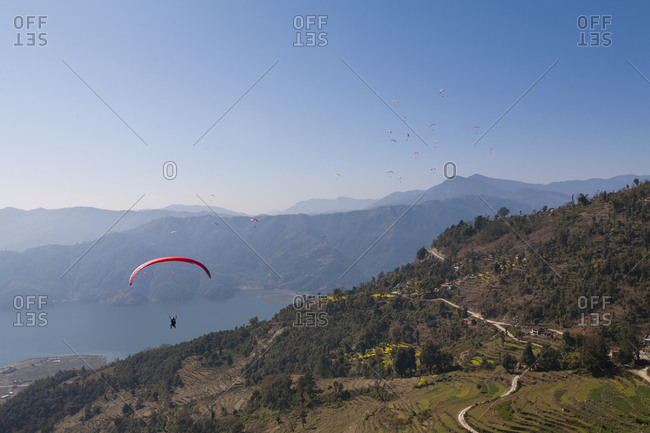 Dozens of paragliders enjoy amazing views of the Himalayas in Nepal above Phewa lake