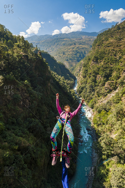 A woman jumps a bungee backwards at The Last Resort in Nepal with the Bhote Kosi river far below