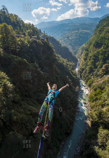 A woman screams with excitement as she jumps a bungee backwards at The Last Resort in Nepal with the Bhote Kosi river far below