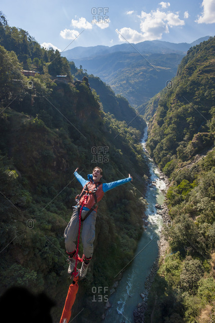 Central region, Nepal - November 7, 2012: A man screams with excitement as he jumps a bungee backwards at The Last Resort