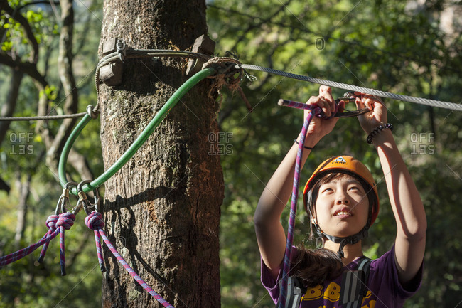 Central region, Nepal - November 7, 2012: A girl practices using carabiners on a high ropes activity course at The Last Resort
