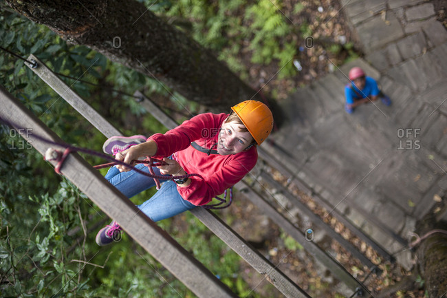 A woman climbs up a giant ladder on a high ropes activity course at The Last Resort in Nepal