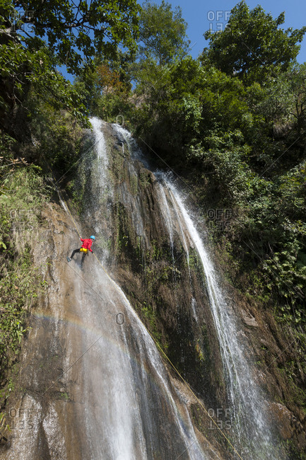 A woman rappels down a waterfall during a canyoning excursion at The Last Resort in Nepal