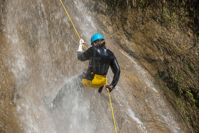 A girl gets soaked under a waterfall as she rappels down a rope canyoning in Nepal