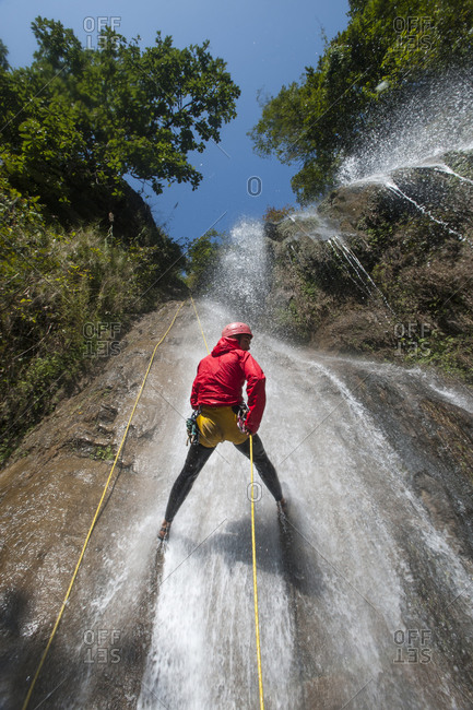 A man rappels down a waterfall while canyoning in Nepal