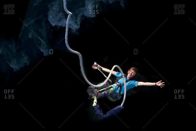 A girl smiles for the camera while bouncing back on a bungee jump at The Last Resort in Nepal