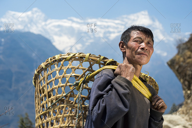 A Nepali man in the Everest region carrying a Doko which is a traditional style of basket made of bamboo and carried on the head with a Namlo or head strap with views of Kongde peak in the distance